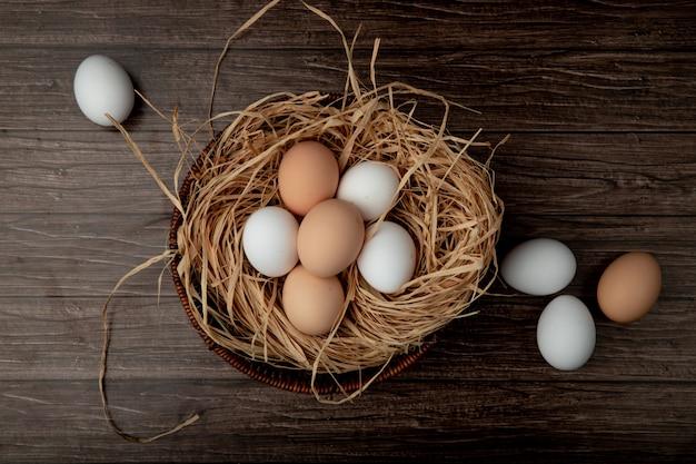 Canasta de huevos en el nido con huevos alrededor de mesa de madera