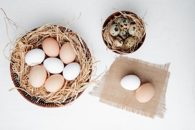 Canasta de huevos en el nido y tazón de huevos en la mesa blanca