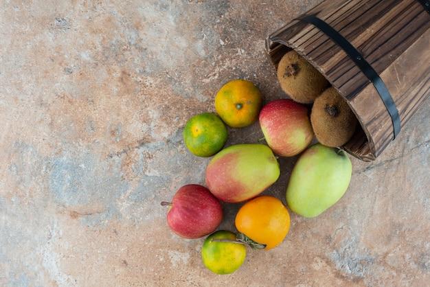 Una canasta de madera con frutas dulces frescas en mesa gris.