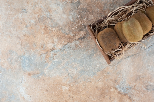 Una canasta de madera de kiwi fresco sobre mesa de mármol.
