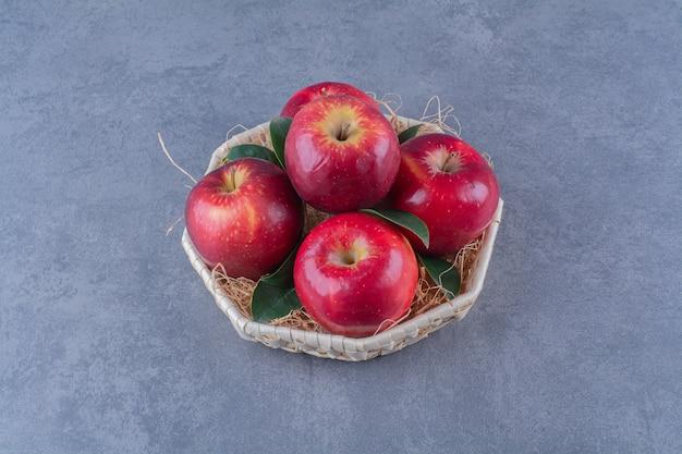 Una canasta de manzanas y hojas sobre la mesa de mármol.