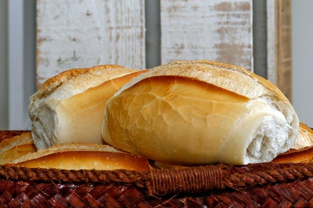 Canasta de pan francés sobre fondo de madera rústica