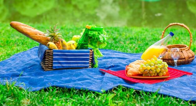 Canasta de picnic con frutas, pan y botella de vino blanco.