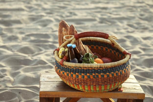 Canasta de picnic llena de bocadillos y bebidas en la playa.