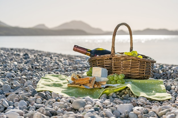 Canasta de picnic con vino, queso y uvas.