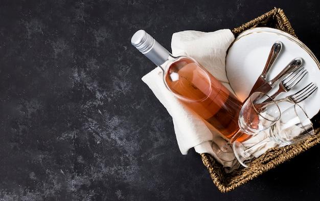 Canasta con vino y vajilla con espacio de copia