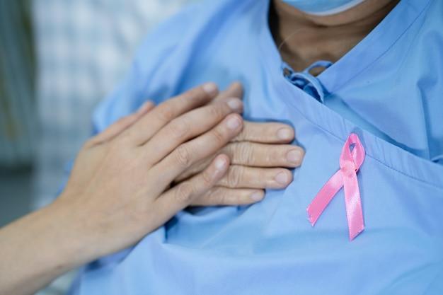 Cáncer de mama, lazo rosa en la paciente asiática senior para apoyar la conciencia.