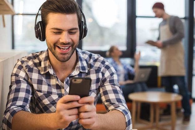 Canción favorita. hombre guapo positivo feliz sosteniendo su teléfono inteligente y escuchando música mientras está sentado en el café