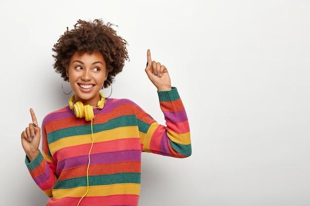 Canción favorita me hace bailar. adorable adolescente levanta las manos, apunta hacia arriba con los dedos índices, disfruta de la música