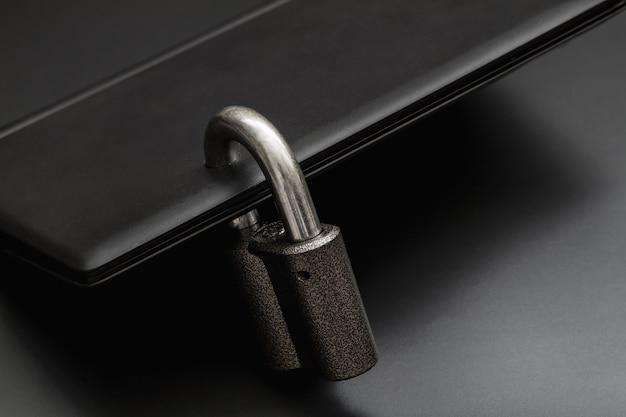Candado de acero bloqueado en un agujero perforado del portátil negro sobre fondo oscuro. concepto de protección de datos personales en una computadora. una computadora portátil está bloqueada con un candado. primer plano, enfoque selectivo