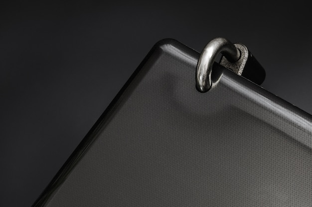 Candado de acero bloqueado en un orificio perforado de la computadora portátil negra