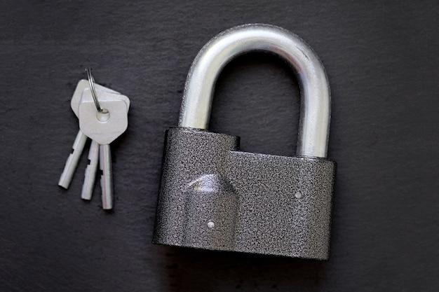 Un candado con asa gruesa y tres llaves de acero sobre un fondo negro