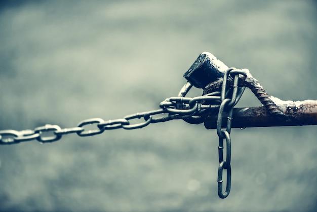 El candado cerrado en la cadena de la cerca marrón es primer en el fondo del asfalto con el bokeh con el espacio de la copia.
