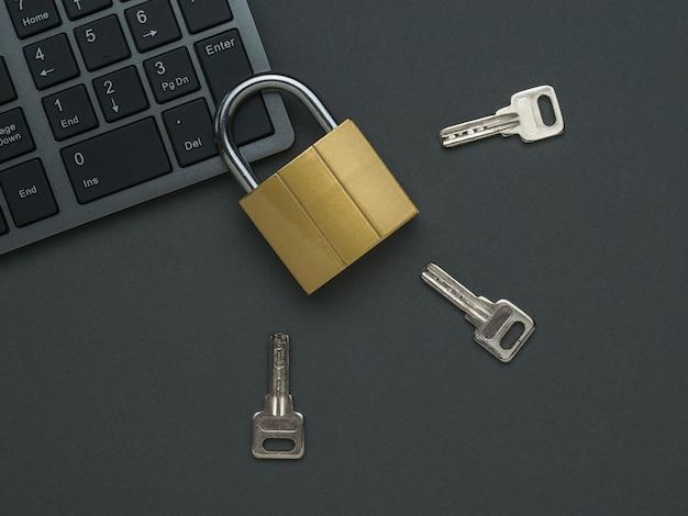 Un candado cerrado en el teclado y tres teclas en una mesa oscura. el concepto de seguridad informática. endecha plana.