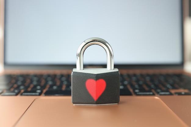 Candado con corazón rojo pintado de pie sobre el teclado del ordenador portátil closeup