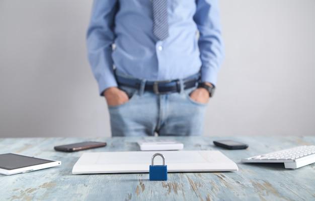 Candado en el escritorio. hombre de pie en la oficina. seguridad de internet y tecnología