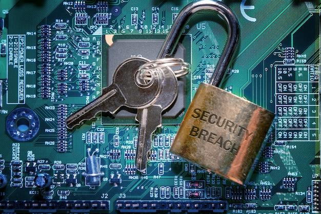 Un candado con la inscripción una violación de seguridad y las llaves en la placa de circuito impreso. concepto de protección de red y seguridad informática de internet.