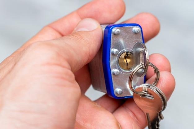Candado de metal en la mano con llaves