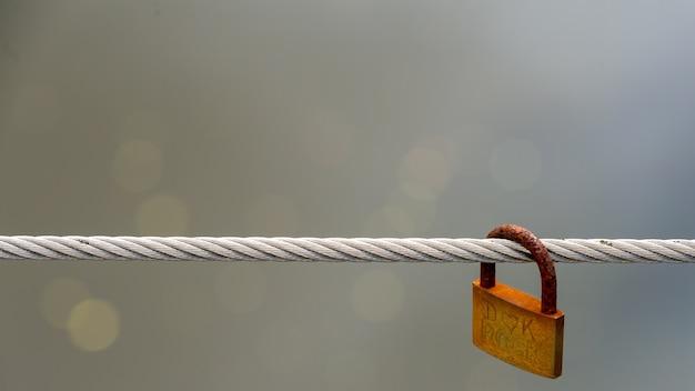 Un candado oxidado cuelga de un alambre.