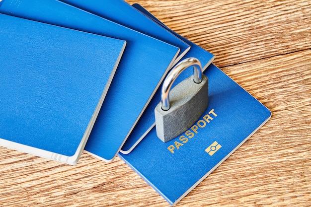 Un candado y pasaportes en la superficie de madera. coronavirus y concepto de viaje. cerrando fronteras entre países por virus. de cerca