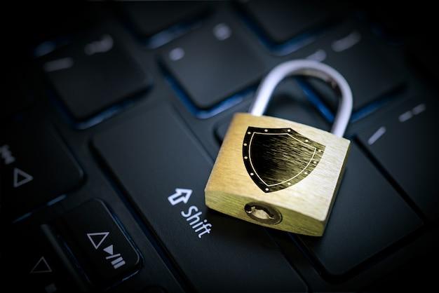Candado de teclado dorado sobre la tecla enter en un teclado de cerca
