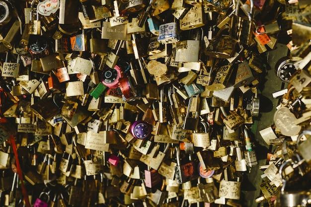 Candados románticos colocados sobre puentes por parejas de amantes enamorados que encadenan sus destinos