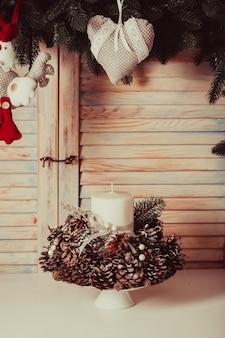 Candelabro de navidad sobre la mesa, decoración con conos