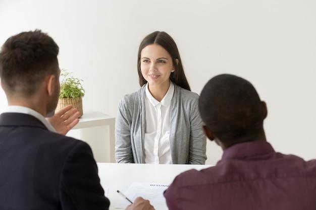 Candidato confiado que sonríe en entrevista de trabajo con diversos gerentes de recursos humanos