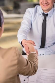 Candidato masculino estrecharme la mano con la empresaria.