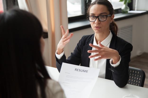 Candidato mujer milenaria confidente en gafas hablando en entrevista de trabajo