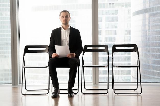 Candidato en el puesto sentado en silla con curriculum vitae