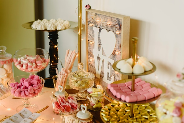 Candy bar bellamente decorado con dulces en un evento vintage.