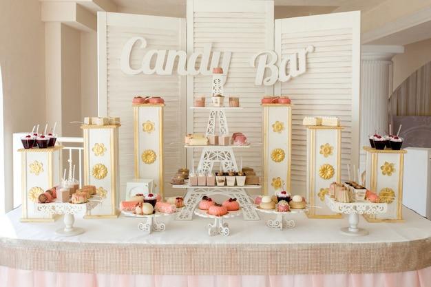 Candy bar delicioso buffet dulce con pastelitos. dulce buffet de vacaciones con cupcakes y otros postres.