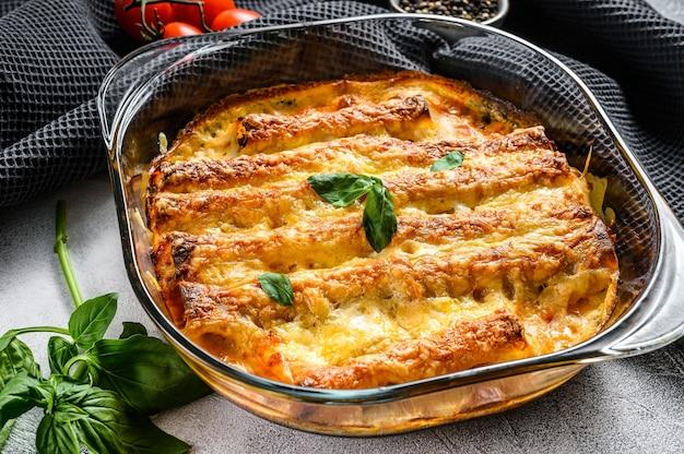 Canelones de carne con salsa de tomate y queso. cocina italiana