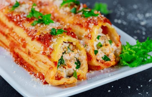 Canelones rellenos con queso ricotta y salsa de tomate.