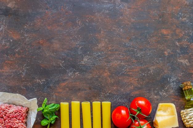Canelones, tomates, carne picada y otros ingredientes. fondo oscuro cocina italiana.