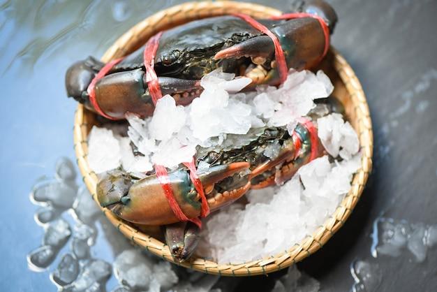 Cangrejo de mariscos en hielo, cangrejo crudo fresco gourmet del océano en la canasta de fondo oscuro en el restaurante