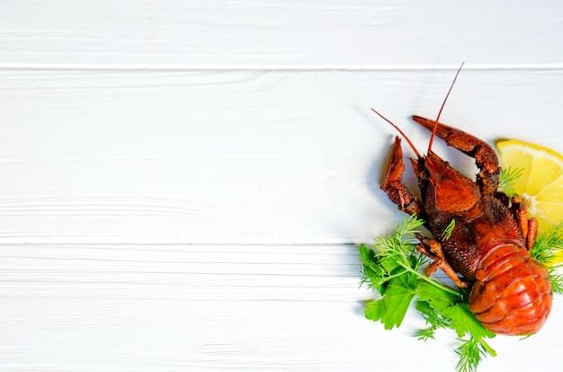 Cangrejo de río sabroso hervido sobre fondo de madera blanca con hinojo (eneldo) y limón en el lateral