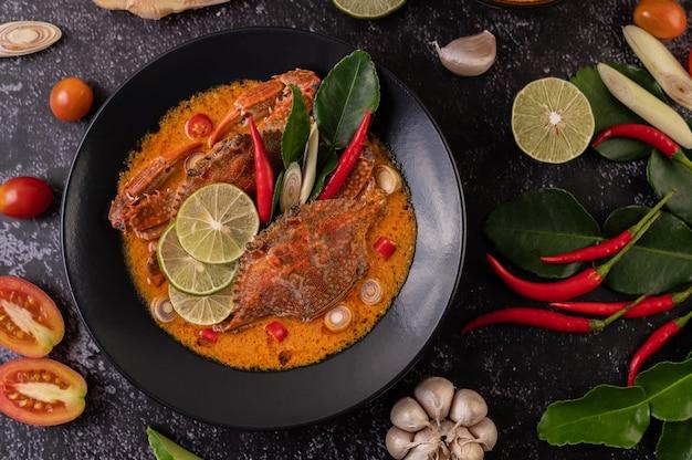 Cangrejo tom yum con limón, chile, tomate, ajo, limoncillo, hojas de lima kaffir en un plato