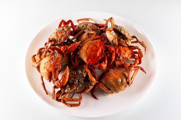 Cangrejos en un plato están aislados por un blanco