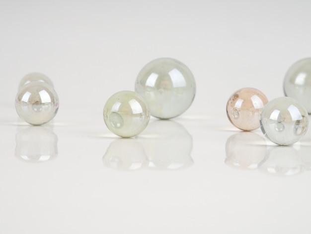 Canicas de vidrio sobre una superficie blanca.