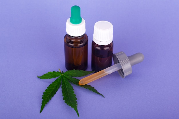 Cannabis medicinal, botellas con tintura de aceite de marihuana sobre fondo azul.