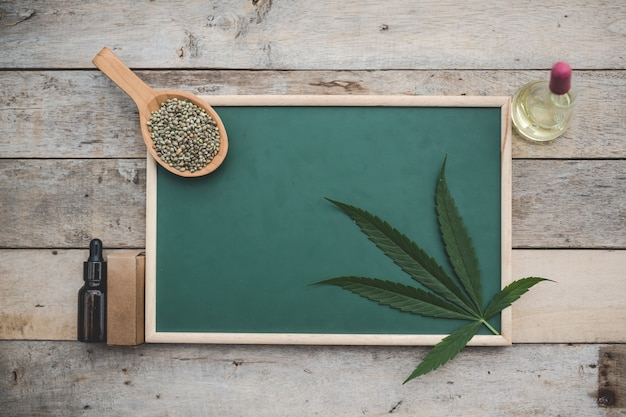 Cannabis, semillas de cannabis, hojas de cannabis, colocadas en el tablero verde y hay aceite de cáñamo al lado en el piso de madera.