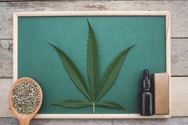 Cannabis, semillas de marihuana, hojas de marihuana, aceite de marihuana colocado en un tablero verde sobre un piso de madera.