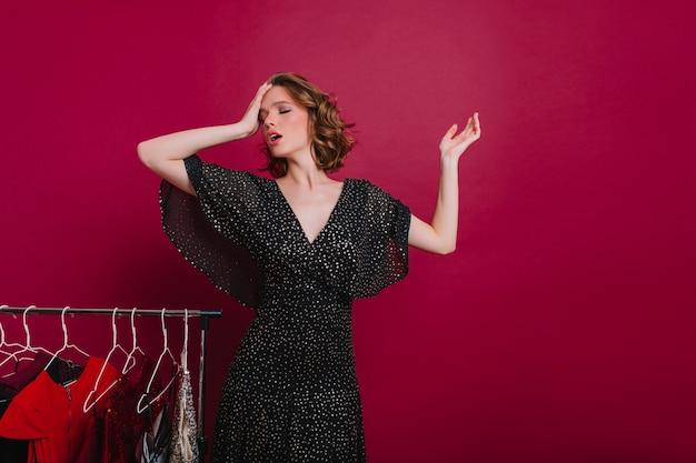 Cansada mujer de pelo corto de pie con los ojos cerrados en el vestidor