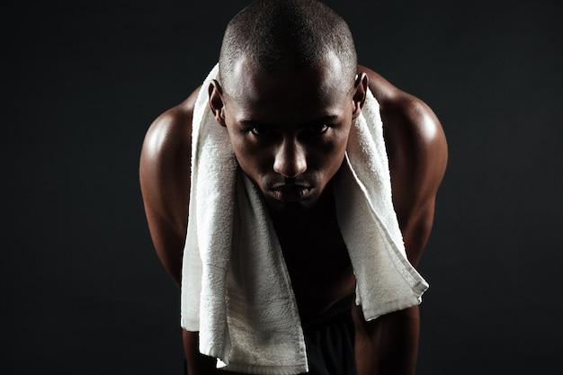 Cansado afroamericano deportista con una toalla sobre sus hombros, relajarse después del ejercicio