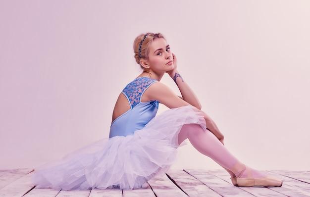 Cansado bailarín sentado en el piso de madera