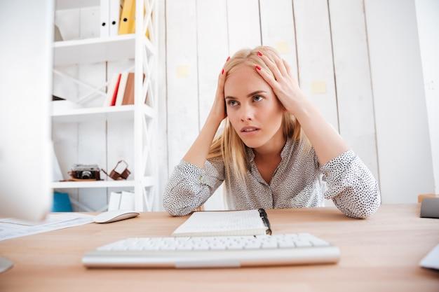 Cansado bastante joven empresaria sentada y teniendo dolor de cabeza en la oficina