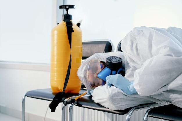 Cansado del desinfectante masculino de día laboral duerme en sillas en el vestíbulo de la oficina. lucha contra el coronovirus.