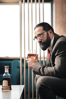 Cansado después del trabajo. hombre de negocios barbudo maduro que se siente extremadamente cansado después del trabajo y beber alcohol